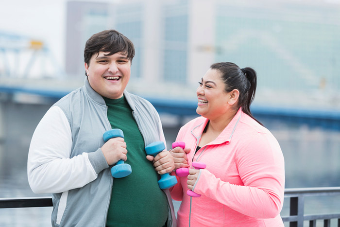 Fat girl and boy doing exercise